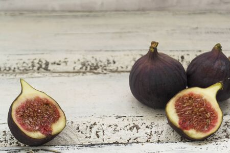 Three fresh figs on a wooden white table. One fig is cut in halves and its flesh is visible. Located in a group. The concept of urge.