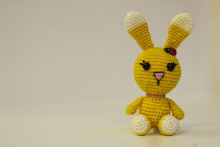 Amigurumi yellow hare sitting on a white background. Needlework concept. There is a place for text
