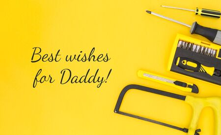 Happy inscription - Best wishes for Daddy with work tools on a yellow background. Congratulations and gifts. View from above. Father's day greetings concept.
