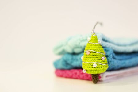 Handmade Christmas knitted gift. Amigurumi toys. Close-up of a Christmas tree knitting with needles on a blurred background. Colorful threads. Copy space.