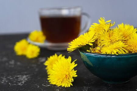 dandelion flowers and healthy tea on a black table. Blurred background, copy space. Summer breakfast and tea Banque d'images