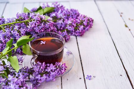 Cup of tea with lilac flowers on a wooden white background. Mocap for postcards. Spring time. Vase with lilacs. Copy space for text. The concept of holidays and good morning wishes. 免版税图像
