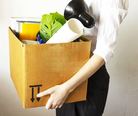 lose job concept. Hand holds box of fired worker. In a box they lay documents, folders, a flower, stationery, a table lamp. Woman worker in a white shirt holds a box. 免版税图像