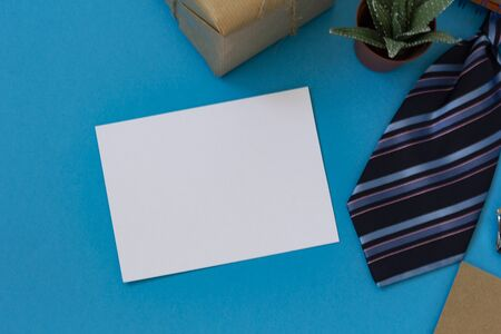 Happy fathers day. Flat layout with congratulations, mens striped tie, box in kraft paper, notebook, sheet for text, a juicy flower.