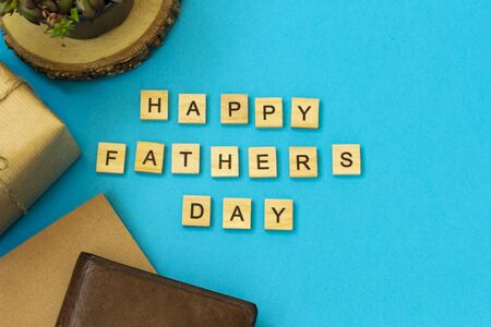 The inscription of wooden letters Happy Fathers Day. Flat layout with congratulations. On a blue background, a box in kraft paper tied with a plait, brown leather partman, a flower in a pot, a notebook. Reklamní fotografie