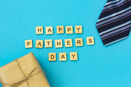 The inscription of wooden letters Happy Fathers Day. Flat layout with congratulations. On a blue background are a striped tie, a box in kraft paper.