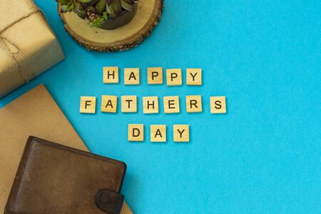 The inscription of wooden letters Happy Father's Day. Flat layout with congratulations. On a blue background, a box in kraft paper tied with a plait, brown leather partman, a flower in a pot, a notebook.
