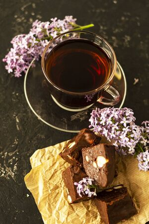 A piece of homemade chocolate cake on crumpled craft paper, with nuts on a black texture table. A cup of tea and lilac flowers decorate a delicious tea party. Copy space. Archivio Fotografico