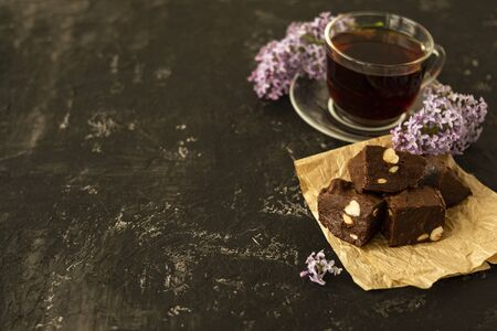 A piece of homemade chocolate cake on crumpled craft paper, with nuts on a black texture table. A cup of tea and lilac flowers decorate a delicious tea party. Copy space. 스톡 콘텐츠