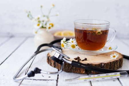 Decoction of chamomile, dried flower in flower tea and a phonendoscope, sliced lemon on a white wooden background. Health concept, prostate treatment, doctor prescribing treatment.