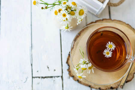 A cup of chamomile and herbal tea with chamomile flowers on white wooden planks. A vase of white flowers stands nearby. Copy space Banque d'images