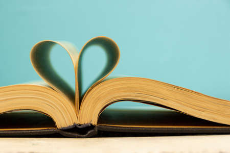The pages of the book are curved in the shape of a heart. Opened book on a blue background. Back to school theme concept. Bibliophile. Archivio Fotografico