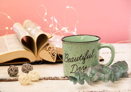 Mint tea mug. On the mug is the inscription of a beautiful day. Nearby lies an open book with heart-shaped pages. Garlands, a eucalyptus branch, decorative balls, and a wooden heart decorate the composition. Pink background.