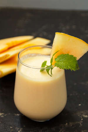 Melon milk shake on a black background. Ripe sliced melon is lying nearby. The smoothie glass is decorated with a sprig of mint and melon crumbs. Summer healthy food concept.