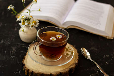 English tea with chamomile stands on a wooden frame and a teaspoon and an open book for reading lies on a black background. Nearby is a white vase with summer chamomile flowers.