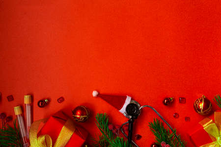 Medical Christmas banner with pills, stethoscope, test tubes, gift box, Santa hat, Christmas toys, heart, and a Christmas tree on a red background. Copyspace. The new year's cure is categorical. Christmas medical flatly.