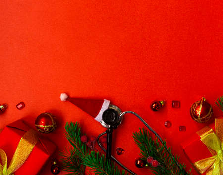 Christmas banner with a Phonendoscope wearing a Santa Claus hat. Nearby are red balls, a heart, a gift box, branches of a Christmas tree, and medical test tubes. Medical banner concept for New Year. The colors are red and gold. Copy space.
