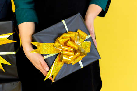 Wide banner. Female hands in dress holding gift box over copy space yellow color background, celebration sale concept womens day and gifts.