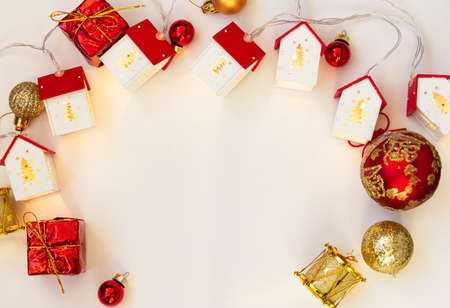 Christmas frame. Christmas balls, garlands, red and gold decorations on a white background. Flat lay, top view, copy space.