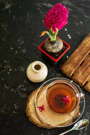 A cup of tea in a transparent cup with spring hyacinth flower on a black background. The mug stands on a wooden frame, next to it lies a metal spoon and a white vase. Copy space.