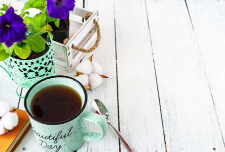 Closeup of a cup of tea on a wooden white table with blur background, front blur. Flat lay. Still life of a flower, a book, a box of cotton. Spring tea. Copy space.