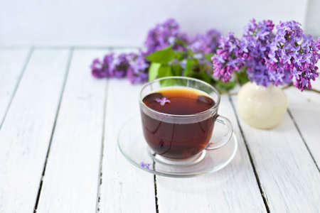 Delicate setting of the morning tea table with lilac flowers, a transparent cup of tea and a saucer and a white vase on a white wooden board. Copy space. Spring breakfast concept. Banco de Imagens