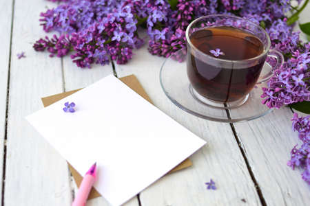 Delicate morning tea table setting with lilac flowers, a transparent cup of tea and a saucer and a white vase, white and craft paper for notes, and a pink pen on a white wooden table. Mockup. Copy space. Spring breakfast concept. Banco de Imagens