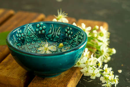 A blue oriental Turkish bowl with transparent water on a background of white cherry flowers on a wooden board and a black background. Copy space. Spring holiday concept