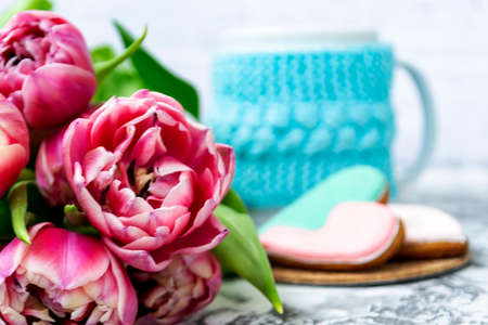 Bouquet of pink tulips, a cup of tea, and sweet gingerbread cookies in the shape of a heart on a light background. Copy space. Spring holiday concept, Valentine's Day Banco de Imagens