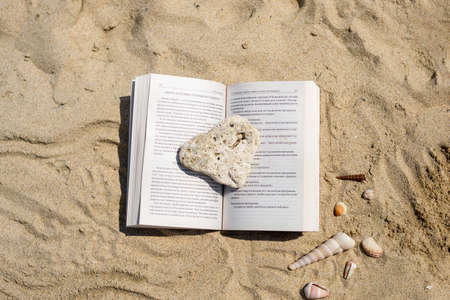 An open book crushed by a stone lies on the sand on the beach. Summer vacation on the beach.