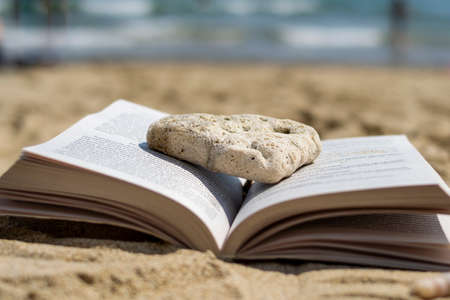 An open book crushed by a stone lies on the sand on the beach. Blurred background. Summer vacation on the beach. Banco de Imagens