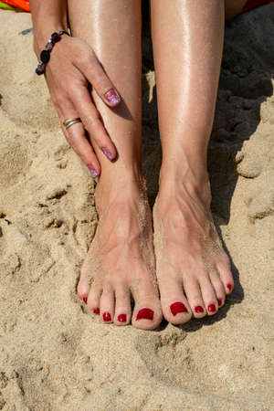 Woman legs with red pedicure relaxing on the sand. The hand strokes the leg. Summer beach.
