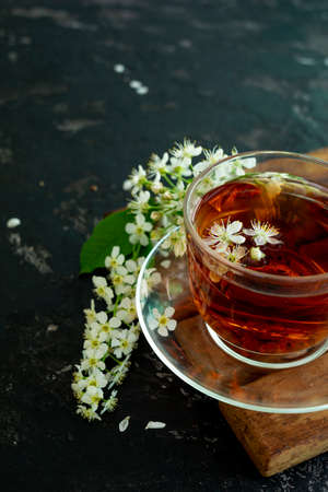 A transparent cup of teapot tea with a saucer and a white bird cherry flower on a black background. Copy space. Spring breakfast.