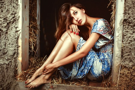 bowed head: girl in the hay in a dress sits with his head bowed, embracing the feet