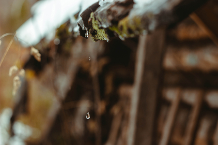 trickle down: A drop of water drips with old wooden roof. Snow is melting. Spring. Stock Photo