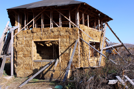 a house with a straw: hexagonal house from straw bales with a roof