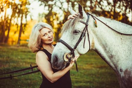 caresses: portrait attractive woman full length next horse