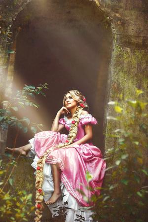 Mooie jonge vrouw met lange haren gevlochten in een vlecht zitten in het raam van de toren.