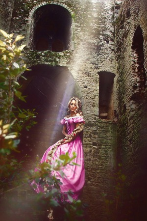 rapunzel: Beautiful young woman with long hair braided in a braid sitting in the window of the tower.