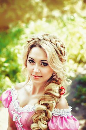 guadaña: Hermosa mujer joven con el pelo largo trenzado en una trenza, sentada en el bosque.