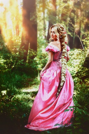 Beautiful young woman with long hair, twisted into a braid, walks in the woods.