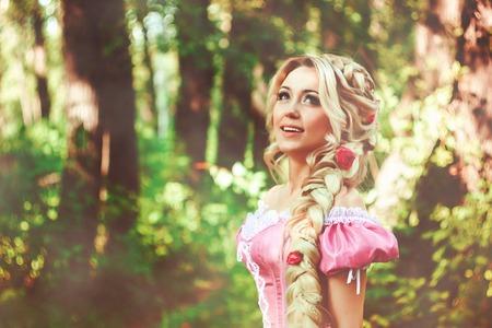 Mooie jonge vrouw met lang haar, gedraaid in een vlecht, wandelingen in het bos.