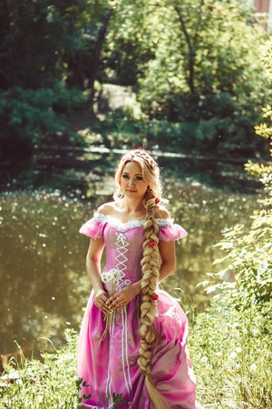 rapunzel: Beautiful girl with long hair braided in a braid, standing by the lake in pink long dress.