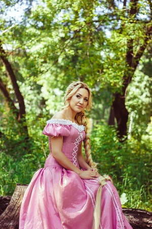 rapunzel: Beautiful young woman with long hair braided in a braid, sitting in the woods.
