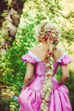 Beautiful girl with long hair braided in a braid, in a beautiful hairstyle in a corset and a magnificent pink dress standing with her back in the woods.