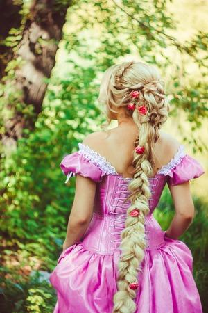 guadaña: Hermosa chica con el pelo largo trenzado en una trenza, en un bonito corte de pelo en un corsé y un magnífico vestido rosa de pie de espaldas en el bosque. Foto de archivo