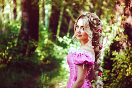 rapunzel: Beautiful young woman with long hair, twisted into a braid, walks in the woods.