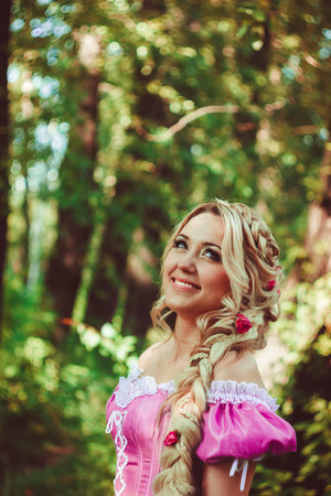 rapunzel: Beautiful young woman with long hair, twisted into a braid, walking and laughing in the forest.