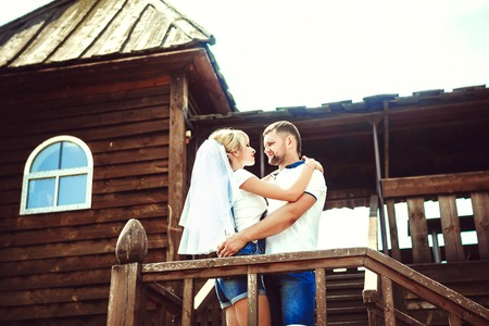 Happy young bride and groom. Wedding in rustic style. They embrace near the wooden porch. Stock Photo