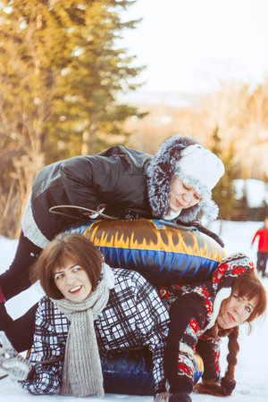 girls play with each other in the winter on an inflatable circle